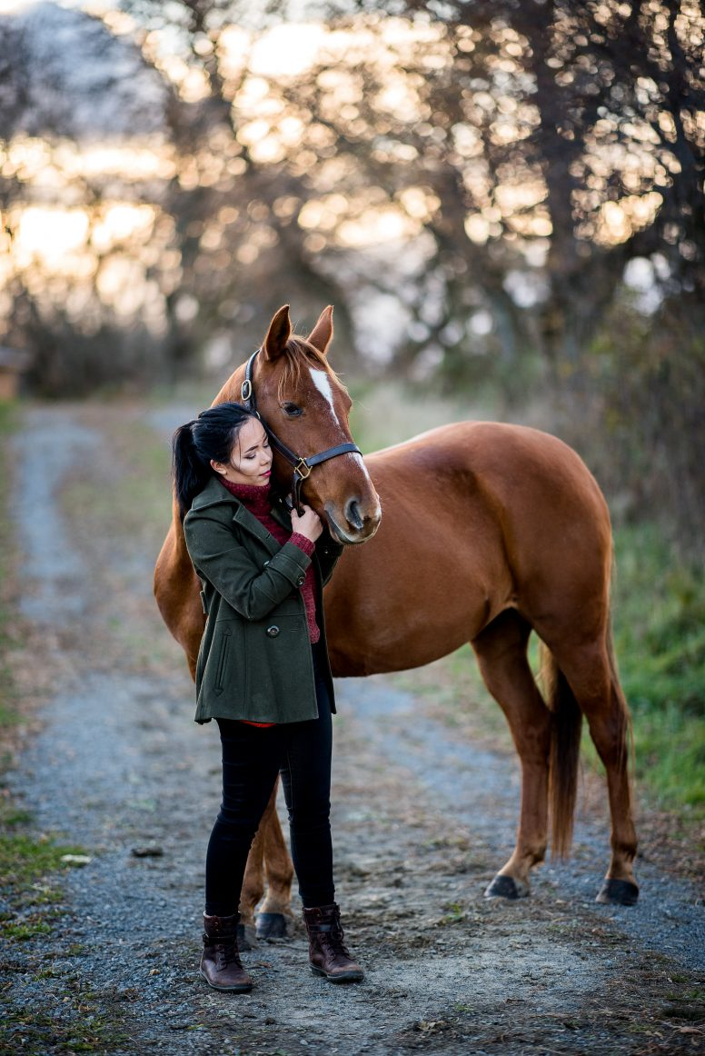 girl with green jacket and chestnut horse